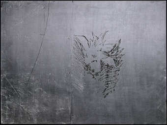A black painted plywood panel covered with aluminum leaf.  Portions of the leaf have been removed...