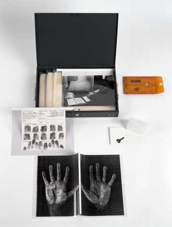 a metal box containing documentation of Bruce Conner being fingerprinted.   For installation one...
