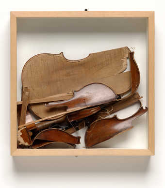 A wood box containing a smashed violin.