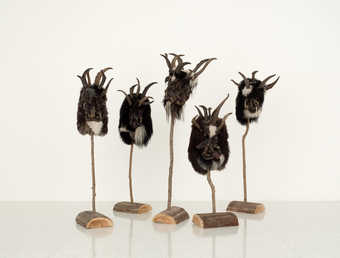 Artist created versions of Krampus Masks, each displayed on a single branch secured into a log.