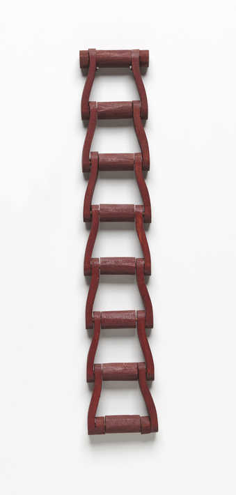 A carved wooden chain painted with an oxblood colored painted.