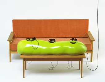 Couch placed in front of a table holding a green plastic form containing three sets of...
