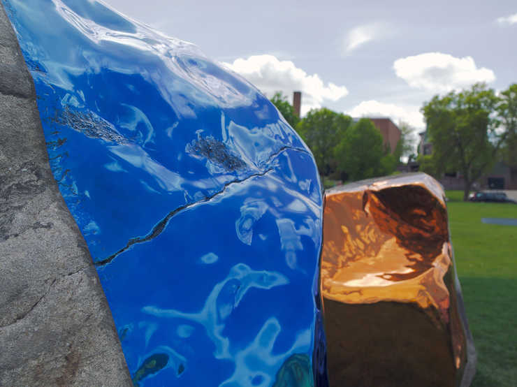 Four large boulders, each containg a sheer of mirror polished, colored stainless steel, The...