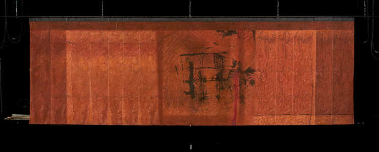 DECOR: Smaller rectangular drop with a burnt orange back ground and an abstract design in black...
