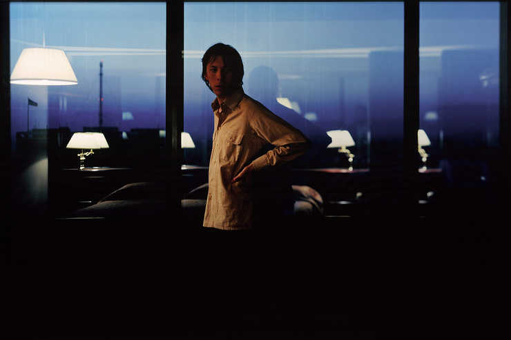 A man standing in front of a curtain wall of windows, reflected in the windows is the interior of...