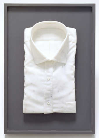 Carved marble in the form of a. folded dress shirt