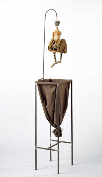 a skeleton figure with a cage like pelvic region, suspended by a hook, hanging over a cloth sack