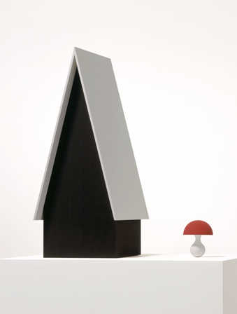 A black house with a white roof next to a red capped mushroom with a white stem.