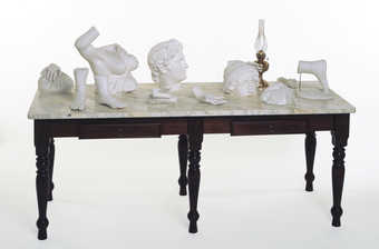 plaster cast body fragments and a gas lamp on a marble topped table
