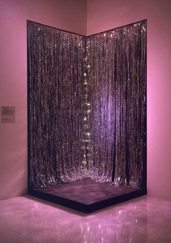 a black plywood platform that stands in front of the two mylar curtains installed in a corner on...