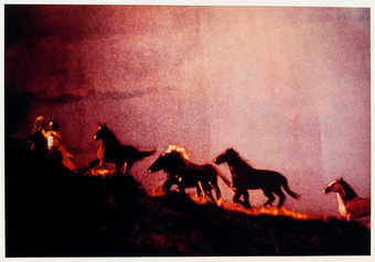 An image of Marlboro men on horseback, riding on a hilltop