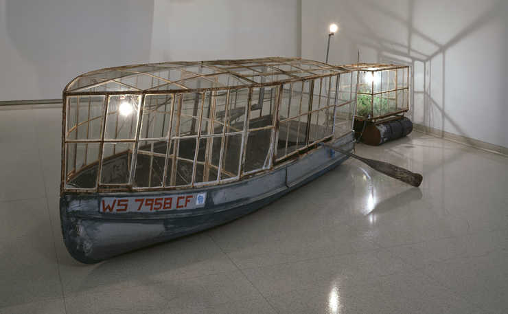an alumininum fishing boat with a glass cover with a glass covered trailer behind.