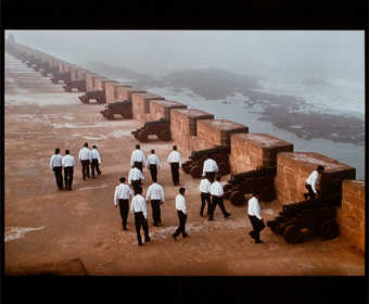 An image of men dressed in white shirts and black pants on the roof of a fortress in Morocco