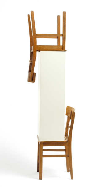 A chair supporting a pedestal with another inverted chair on top.