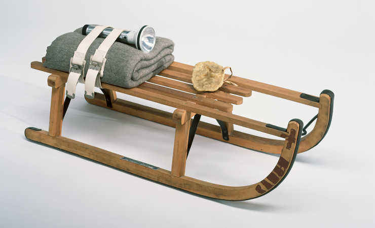 Wooden sled with metal runners and supports, lump of fat tied to top, and  folded felt blanket...