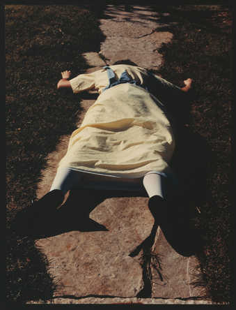 An image of a young woman in a yellow dress and white tights falling down steps.