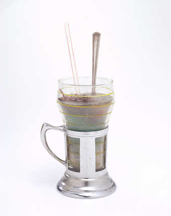 A soda glass and holder filled with blue wax, hair, and meat-like chunks.  A spoon and straw are...