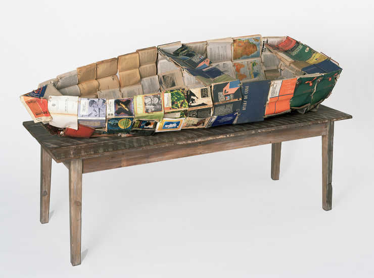 a boat constructed of a metal armature and composed of Cuban text books; boat rests on a wood table