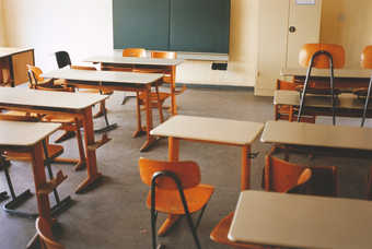 shot of a classroom with desks, chairs, and chalk board
