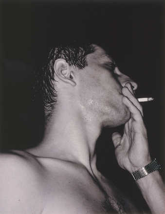 profile shot of a man's head and hand while smoking a cigarette