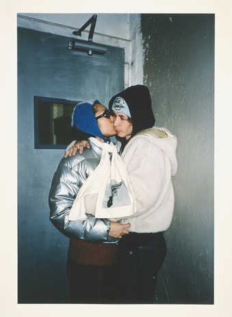 young man and woman kissing in doorway; woman is wearing a silver winter jacket