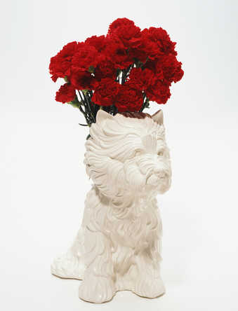 A white ceramic West Highland terrier with a cavity in its back to serve as a flower vase.