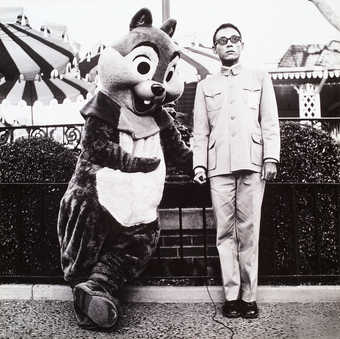 an image of the artist standing with a person dressed in a chipmunk costume