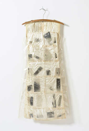 A white satin dress covered with vinyl and cellophane pockets that contain photographic...