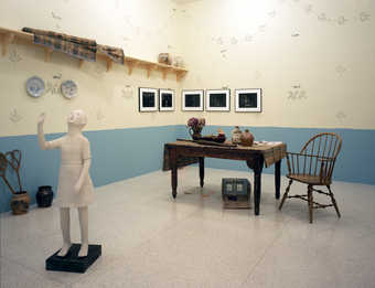 An installation containing stencil painted walls, ceramic vessels, a dining table a winsor chair,...
