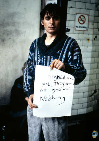 "An image of a man holding a hand written sign that reads ""I Signed On and They Would Not..."