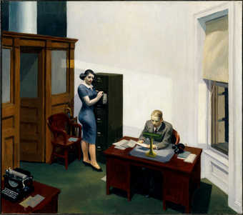Interior of an office.  Man sitting behind a desk reading some papers which he holds with both...