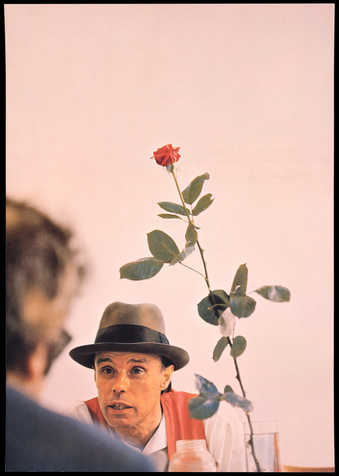 Color offset lithograph from photograph by Wilfried Bauer of Beuys with a red rose at Documenta 5...