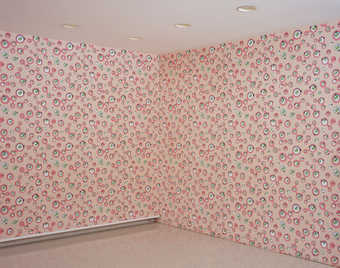 Pink wallpaper with a repeating design of sylized eyes.