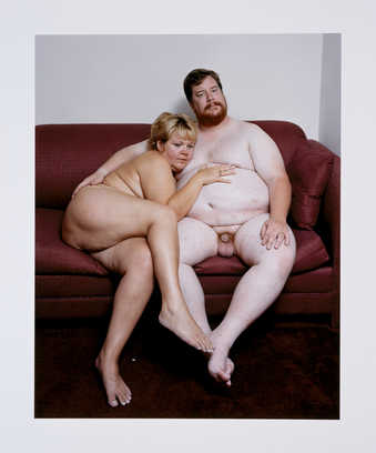 An image of a nude couple seated on a couch.