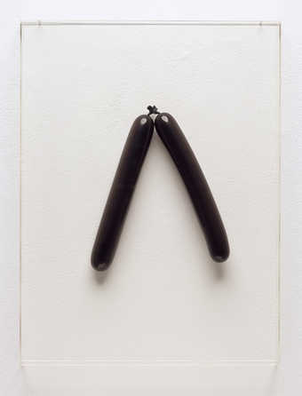Two black balloons inflated and installed to the artist's specifications, behind a...