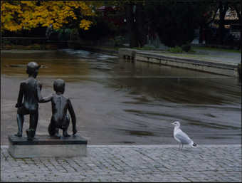 An image of a bronze statue of two kneeling children in front of a pool.  Next to the statue a...