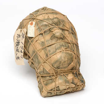 A plaster mask covered with imitation one-thousand-Yen notes, wrapped with a string netting. ...