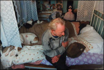 A slighlty out of focus image of the artist's father seated on a bed next to a dog, the...