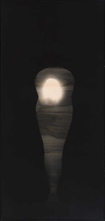 Photogram image of the artist bent at the waste holding a globe of light