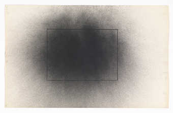A graphite rectangle under a a grey circular spray pattern.